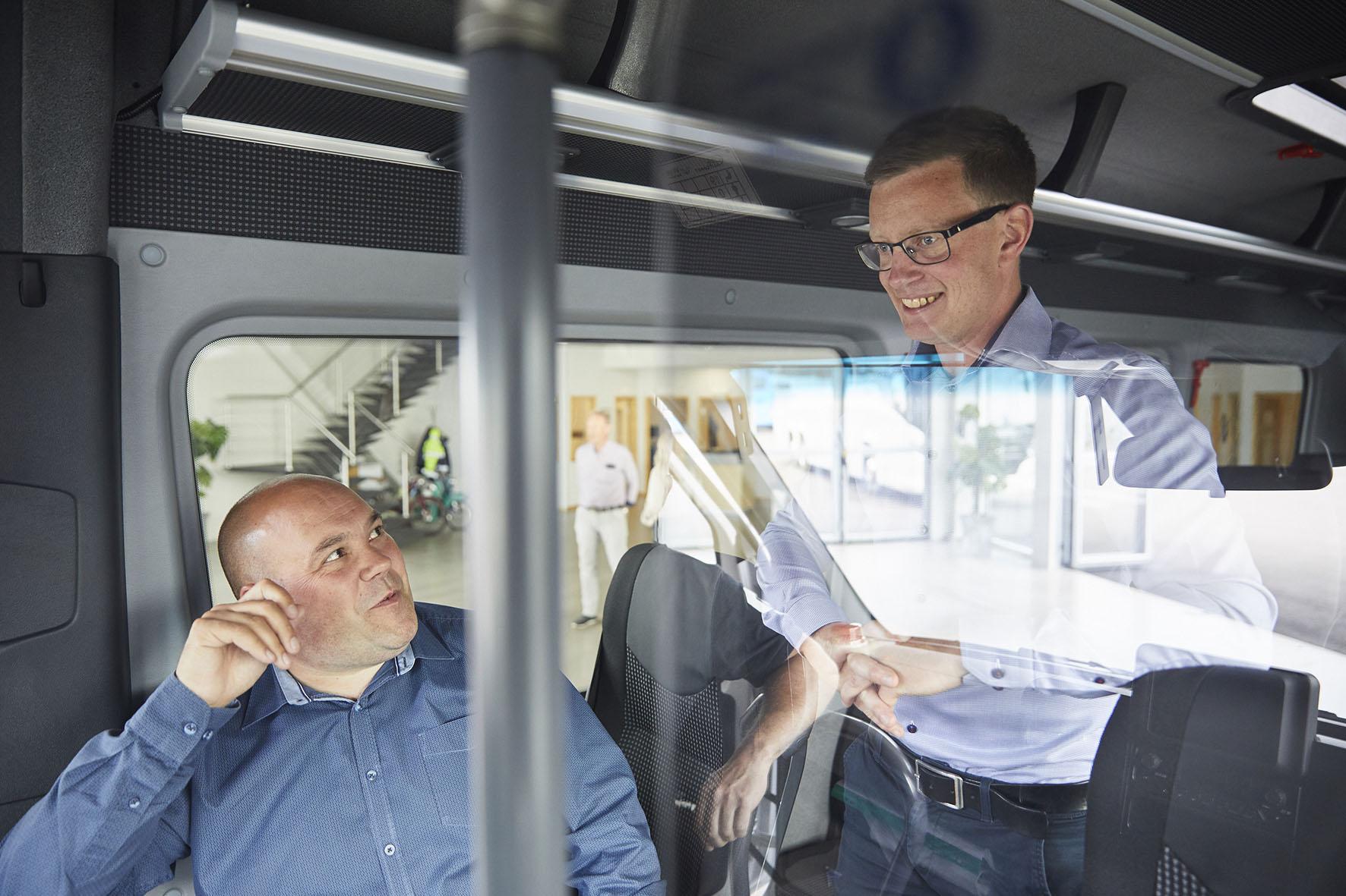 två-män-pratar-glatt-i-buss